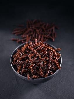 Biologische ongekookte boekweitfusilli pasta op donkere ondergrond. volkoren glutenvrije noedels. gezond voedselconcept.