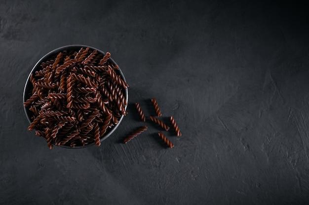 Biologische ongekookte boekweitfusilli pasta op een donkere achtergrond. volkoren glutenvrije noedels. gezond voedselconcept.