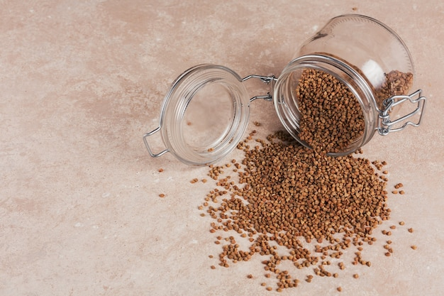 Biologische ongekookte verspreide boekweitkorrel in een glazen pot op een lichtbeige achtergrond. gezond en dieetvoedselconcept.