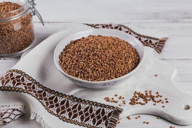 Biologische ongekookte verspreide boekweitkorrel in een kom en glazen pot op een witte houten rustieke achtergrond. gezond en dieetvoedselconcept.