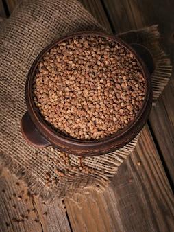Biologische ongekookte verspreide boekweitkorrel in een kom op een rustieke houten achtergrond. gezond en dieetvoedselconcept.