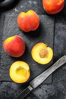 Biologische perziken fruit op een zwarte stenen bord.
