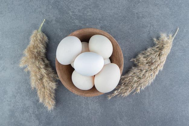 Biologische rauwe eieren in houten kom.