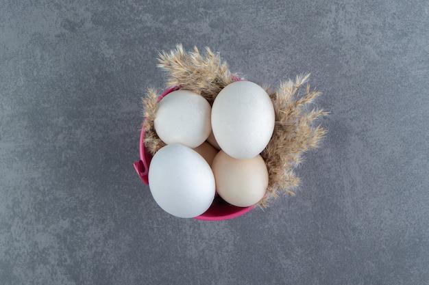 Biologische rauwe eieren in roze kom.