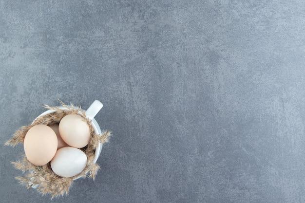 Biologische rauwe eieren in witte mok.