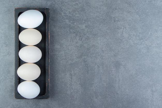 Biologische rauwe eieren op zwarte plaat.