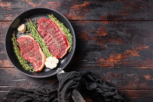 Biologische rauwe picanha rundvleeslapjes vlees op een zwarte plaat