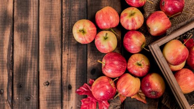 Biologische rijpe rode appels in houten kist. herfstoogst hoorn des overvloeds in het herfstseizoen. vers fruit met houten tafel achtergrond.