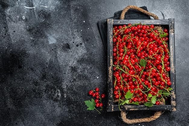 Biologische rode bessen in een houten kist. zwarte achtergrond. bovenaanzicht. ruimte kopiëren.