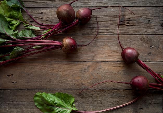Biologische rode biet groente. verse rode biet wortels geoogst op houten. bovenaanzicht
