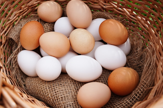 Biologische rustieke witte en bruine kippeneieren close-up op natuurlijke doek in een mand en gele kleine c...