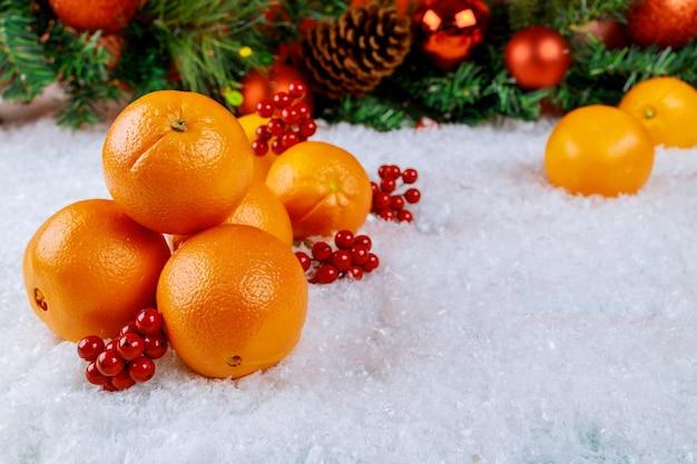 Biologische sinaasappelen in kerstdienblad met ornament. gezond voedselconcept.