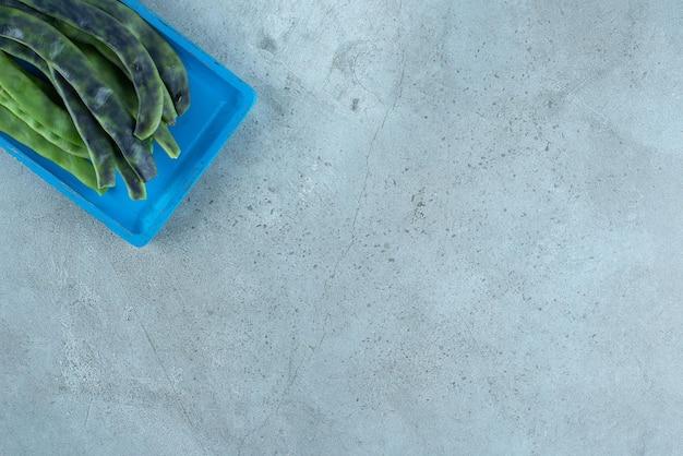 Biologische sperziebonen op blauw bord.