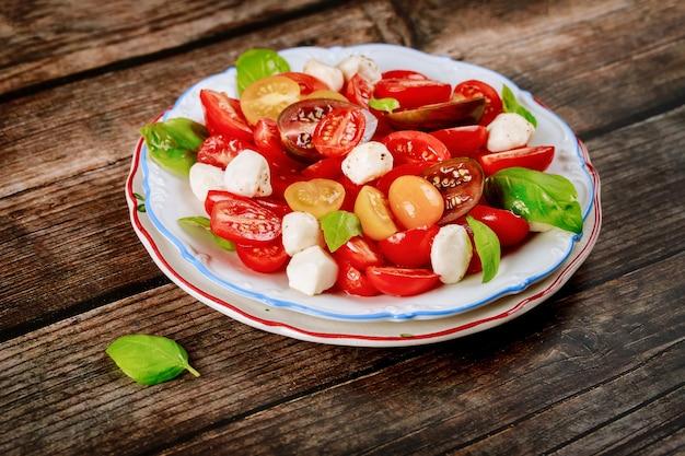 Biologische vegetarische salade met mozarellakaas op witte plaat