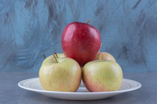 Biologische verse appels op plateon marmeren tafel.