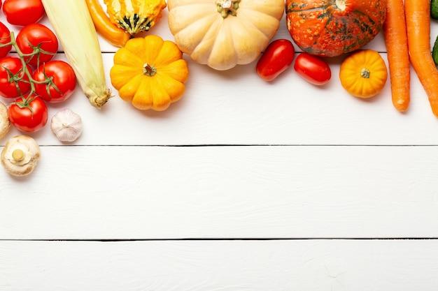 Biologische verse groenten voedsel achtergrond. herfst groenten en thanksgiving day thema. pompoenen, wortelen, tomaten, champignons, komkommers, maïs en knoflook op witte houten tafel. vrije ruimte.
