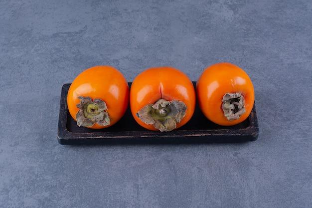 Biologische, verse persimmonvruchten aan boord op marmeren tafel.