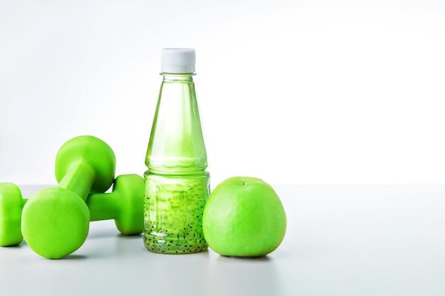Biologische voeding en sportuitrusting op lichtgrijze achtergrond met kopieerruimte. gezonde levensstijl voedsel fitness concept.