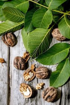 Biologische walnoten, geheel en gebroken, met groene bladeren van de walnotenboom over oude houten tafel. plat leggen, ruimte