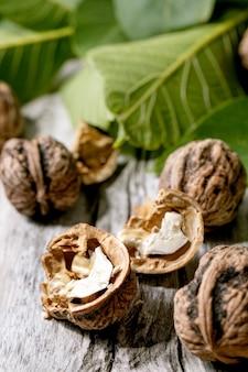 Biologische walnoten, geheel en gebroken, met groene bladeren van walnotenboom over oude houten tafel. detailopname
