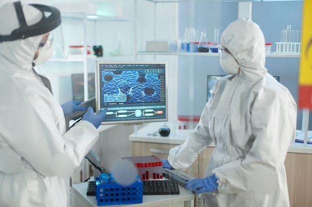 Biologische wetenschappers die een medisch beschermingspak dragen en werken in een microbiologisch ziekenhuislaboratorium
