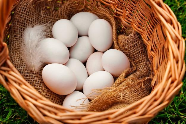 Biologische witte eieren liggen in een rieten rustieke mand