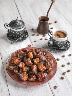 Biologische zoete dadels met siroop en zwarte koffie. ramadan kareem concept vakantie.