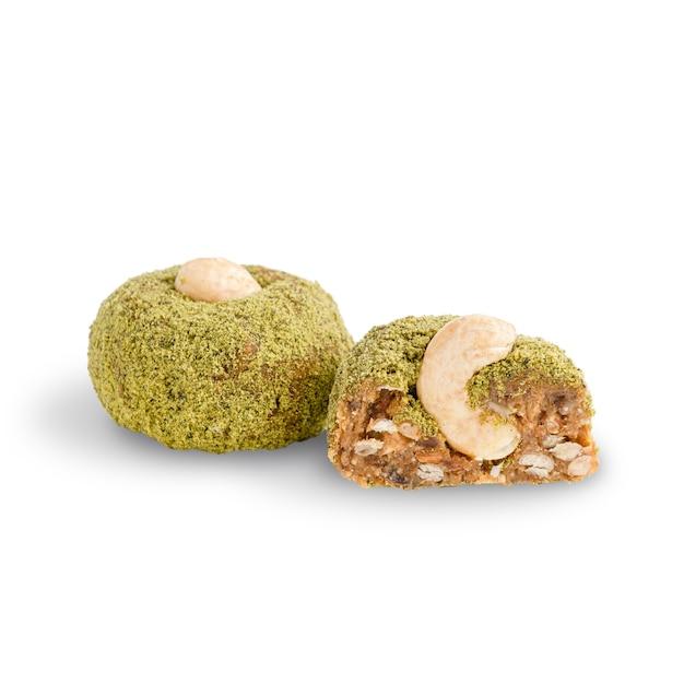 Biologische zoete noten veganistische truffels in groen poeder gemaakt van cashewnoten geïsoleerd op een witte achtergrond