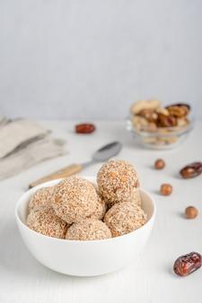 Biologische zoete truffels dessert gemaakt van hazelnoot en dadel fruit geserveerd in kom op witte houten tafel