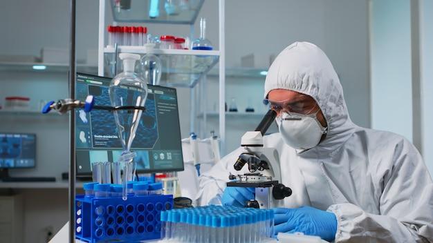 Bioloog-arts in overall die het typen van dna-monsters op pc in modern uitgerust laboratorium controleert. team dat de evolutie van het vaccin in een medisch laboratorium onderzoekt met behulp van hightech- en scheikundige hulpmiddelen voor wetenschappelijk onderzoek