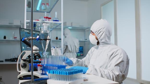 Bioloog-arts in ppe-pak die vloeistofmonsters controleert op pc in uitgerust laboratorium. team dat de evolutie van het vaccin in een medisch laboratorium onderzoekt met behulp van hightech- en scheikundige hulpmiddelen voor wetenschappelijk onderzoek