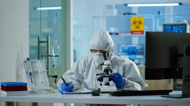 Bioloog in ppe-pak die aan de microscoop werkt en informatie schrijft op het klembord in een uitgerust laboratorium. chemicus die vaccinevolutie onderzoekt met behulp van hightech onderzoek naar diagnose tegen covid19-virus