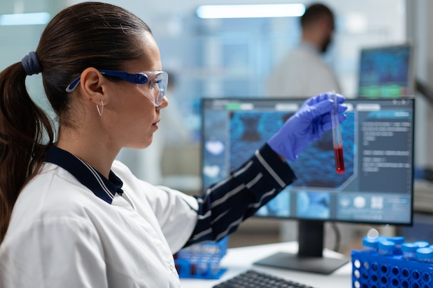Bioloog-onderzoeker die bloedonderzoeksbuis vasthoudt die dna-medische expertise analyseert