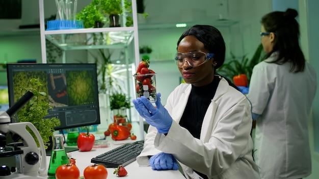 Bioloog-onderzoeker kijkt naar biologische aardbei die fruit onderzoekt voor microbiologie