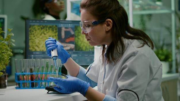 Bioloog-onderzoeker met behulp van micropipet en petrischaaltje