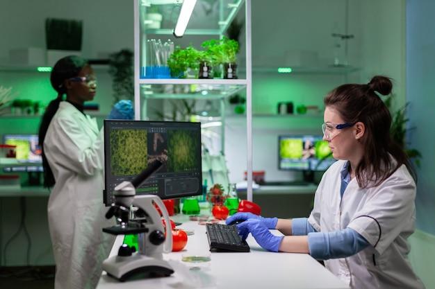 Bioloog onderzoeker vrouw die genetisch gemodificeerde planten op computer analyseert