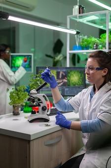 Bioloog-splecialist die met een pincet groen bladmonster neemt taking