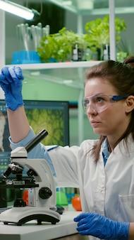Bioloog wetenschapper kijkt naar testmonster met behulp van microscoop voor chemische expertise