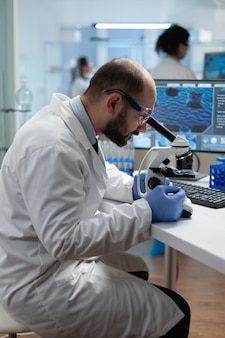 Bioloog wetenschapper man arts die de resultaten van het coronavirus-monster onderzoekt met behulp van een medische microscoop