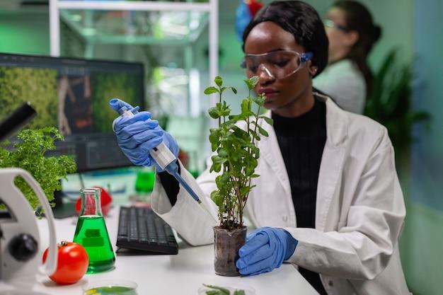 Bioloog wetenschapper praten oplossing van medische kolf op groen jonge boompje voor genetisch experiment. vrouw onderzoeker in witte jas werken in professionele microbiologie laboratorium.