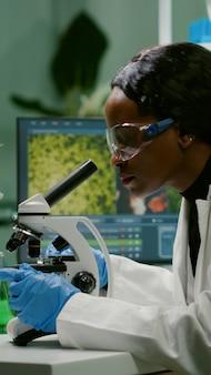 Bioloogvrouw die teststeekproef onder microscoop bekijkt die bij ggo-experiment werkt