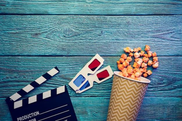 Bioscoop concept. filmklapper, glazen en popcorn op blauwe houten tafel, bovenaanzicht