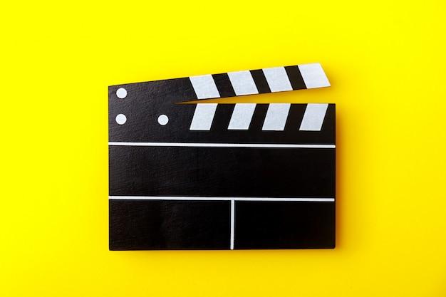 Bioscoop zwarte filmklapper op gele achtergrond. moderne cinematografie, filmmaken.