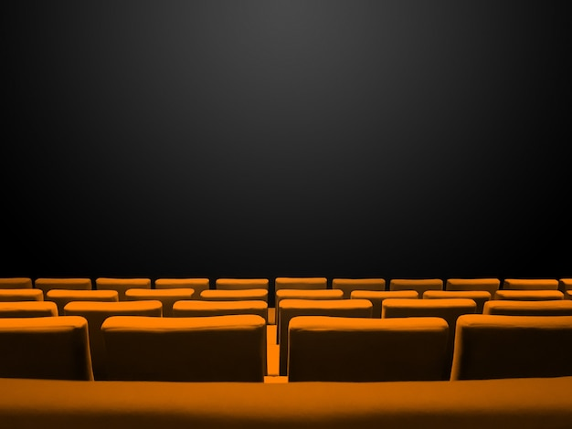 Bioscoopbioscoop met oranje stoelenrijen en een zwarte achtergrond met kopieerruimte