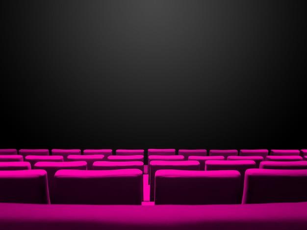 Bioscoopbioscoop met roze stoelenrijen en een zwarte achtergrond met kopieerruimte