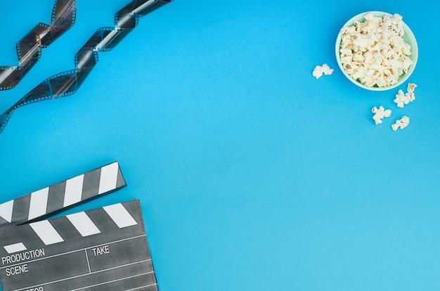 Bioscoopconcept - filmklapper met popcorn en filmstrook op blauwe achtergrond met exemplaarruimte.