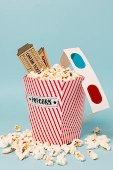 Bioskoopkaartjes en 3d glazen op popcorndoos tegen blauwe achtergrond