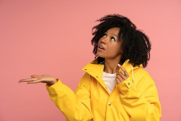 Biracial krullende vrouw in gele regenjas heeft een goed humeur
