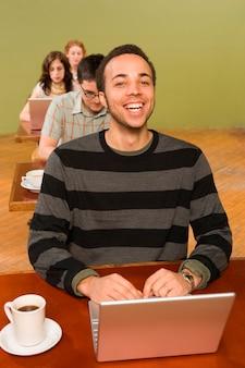 Biracial man aan het hoofd van de rij van laptopgebruikers