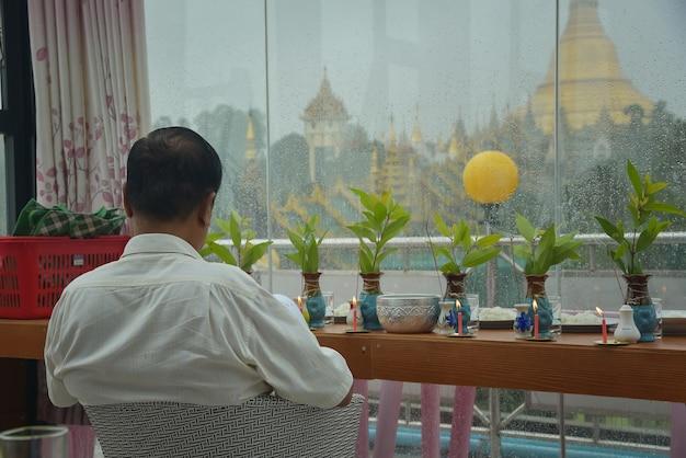 Birmese mannen bidden om gezegend te worden in een huis met uitzicht op de shwedagon-pagode in yangon, myanmar